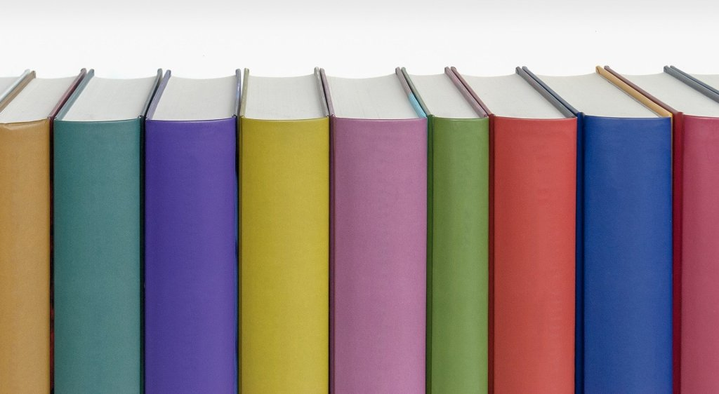 Image of books on shelf with rainbow-coloured spines